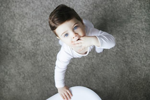 Infant child baby toddler kid in white bodysuit standinging on carpet