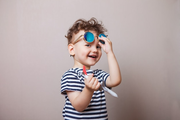 Infant, child with a toy airplane in his hands and sunglasses. tourist