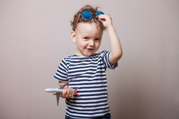 Infant, child with a toy airplane in his hands and sunglasses.