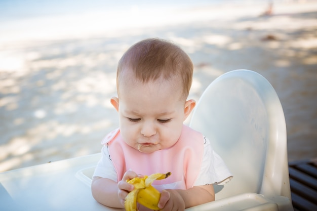 Девочка с энтузиазмом собирает банан ребенок ест фрукты на пляже, сидя на белом детском стуле