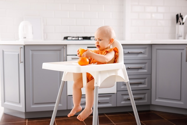 Infant girl sitting in high child's chair eating fruits on white
