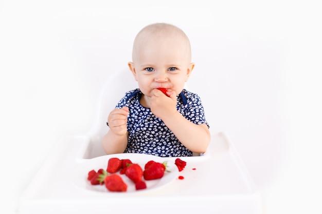 白の果実を食べて高い子供の椅子に座っている幼児の女の子