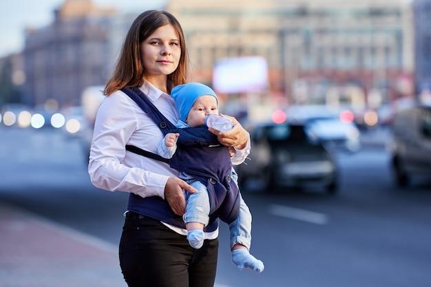 Младенца в слинге кормит мать из бутылочки на открытом воздухе