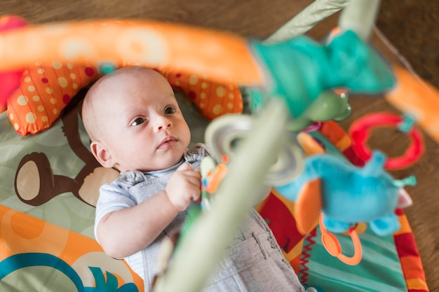Infant lying on developing rug looking at hanging toys