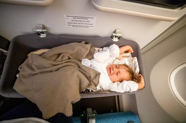 유아 승객 유아는 비행기에서 일어나 특수 아기 요람에서 기지개,