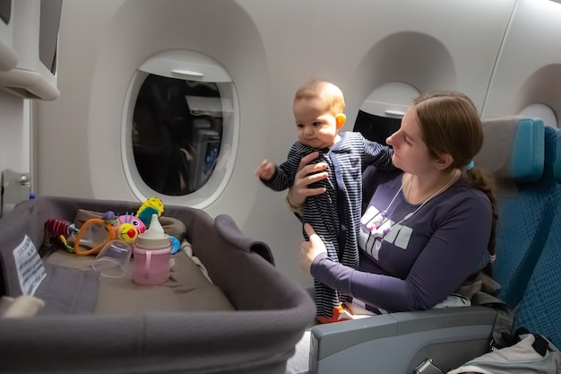 Infant plays on mother hands at the airplane.  interest to special baby bassinet during the flight
