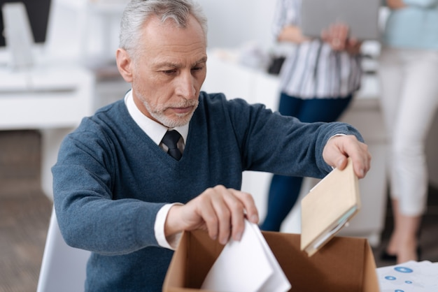 Infatuated office worker wearing blue cardigan holding documents in both hands while wrinkling his forehead