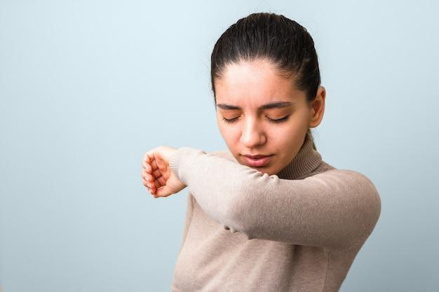 Зараженная женщина с лихорадкой и головной болью, чихая и кашляя