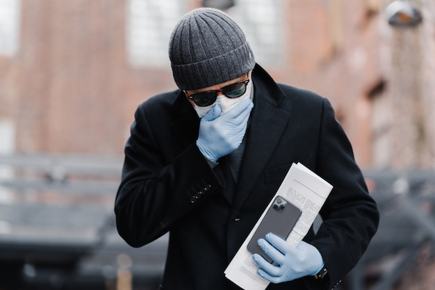 Infected young man has sneezing and coughing, wears disposable protective mask against covid-19, holds modern smartphone and papers, poses outdoor against blurred background. global pandemic concept