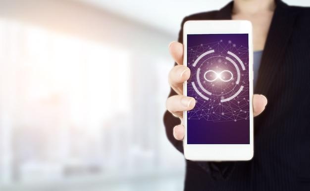 무한 개념입니다. 흐릿한 배경에 디지털 홀로그램 무한대 기호가 있는 흰색 스마트폰을 손에 들고 있습니다.