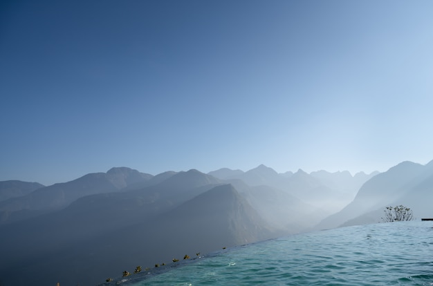 Infinity edge pool with layer of mountain in the background / landscape photo / copy space