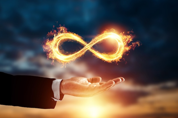Infinity fire symbol over hand of businessman