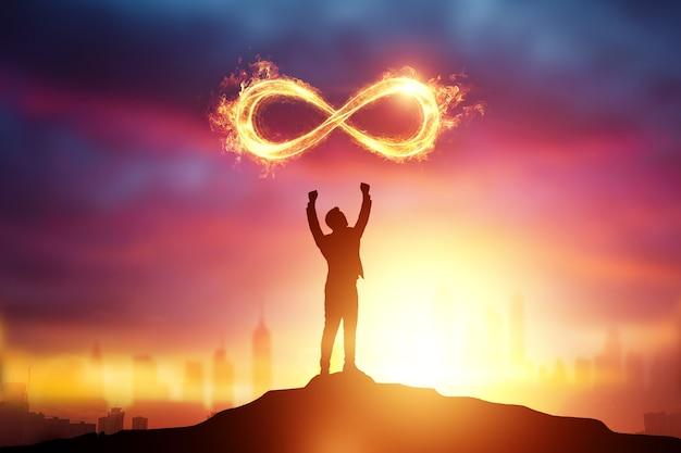 日没のビジネスマンのシルエットの上の無限の火のシンボル。