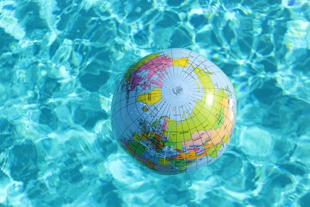 Inflatable ball in globe form in blue water