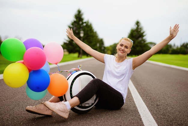 Inflatable balls. woman sit with monowheel in road.