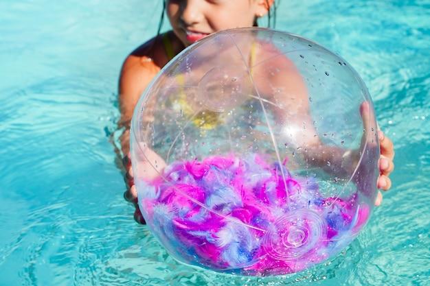 外洋の表面に浮かぶピンクの羽で透明なインフレータブルビーチボール...