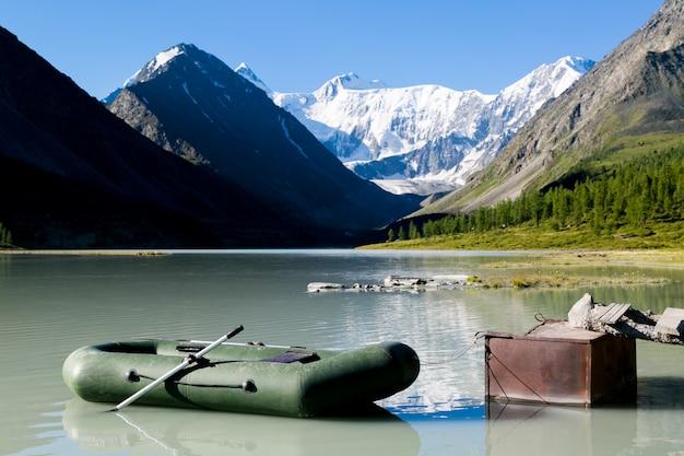 Надувная лодка на берегу озера в горах.