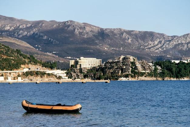 푸른 나무와 산이있는 해안을 배경으로 바다에 풍선 보트