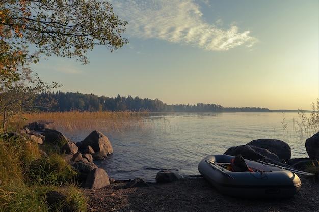 안개 낀 호수 배경에 낚싯대와 구명조끼가 있는 풍선 보트. 여름 저녁.