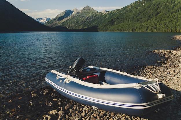 아름다운 그림 같은 호수에 모터가 달린 풍선 보트. 아름다운 산을 배경으로 낚시 보트