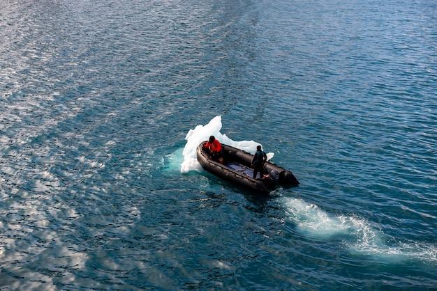 Надувная лодка с одним человеком в арктических водах, шпицберген. толкая лед.