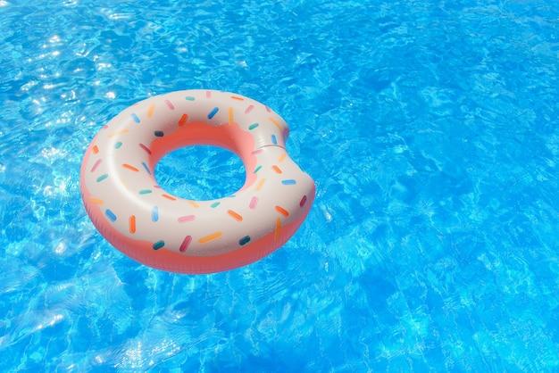 Надувной пончик, плавающий в бассейне Premium Фотографии