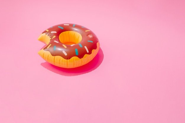 Inflatable doughnut pool toy on pastel pink surface