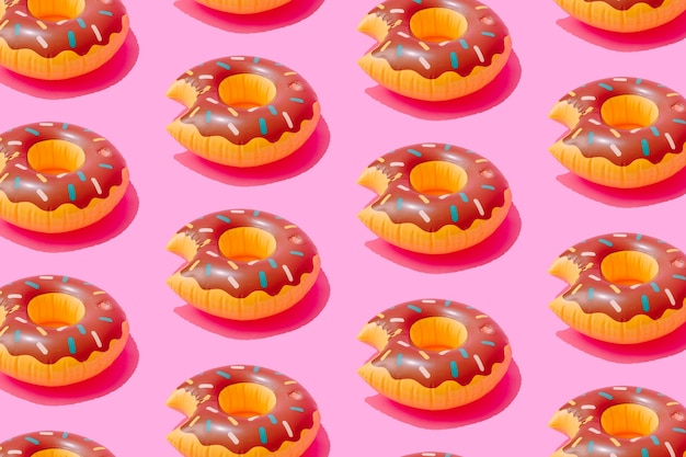 Inflatable doughnut pool toy pattern  on pastel pink surface
