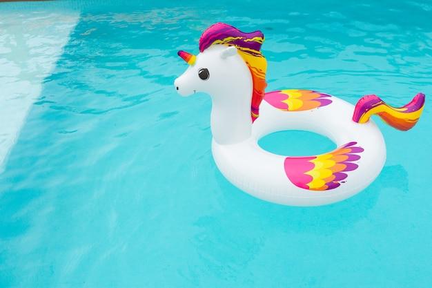 プールでカラフルなユニコーンの形をしたインフレータブルフロート