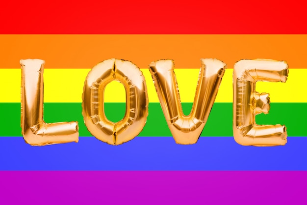 Inflatable golden balloons, letters love on lgbt pride flag background