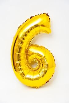Надувная цифра 6 сверкающего металлического золотого цвета на белом фоне