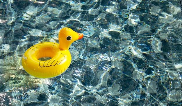 Надувной желтой утки в бассейне. летний фон концепция