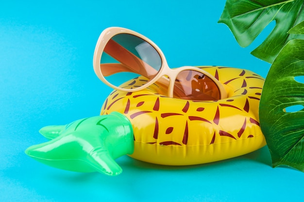 Inflatable pineapple on blue background with sunglasses and monstera leaves.