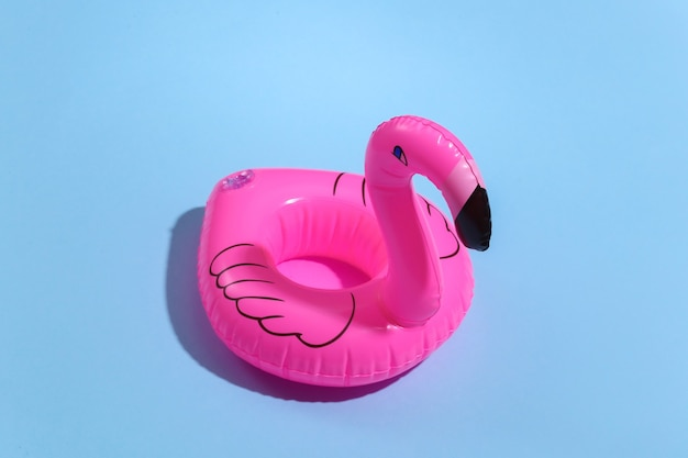 Inflatable pink flamingo on blue sunny background. summer vacation concept. minimalism