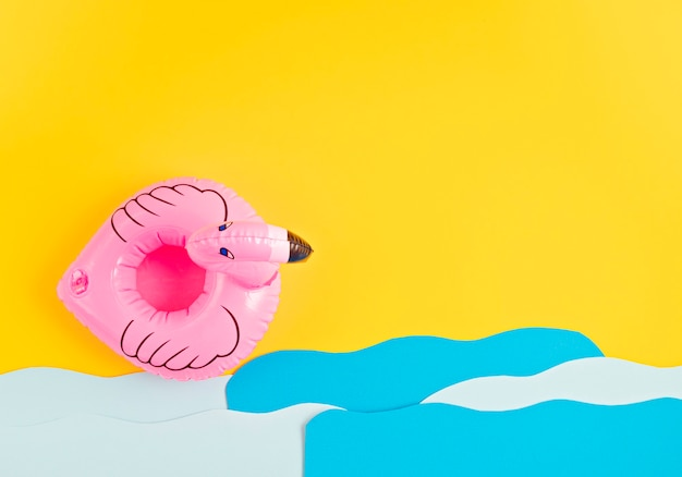 Inflatable pink flamingo, paper sea waves. summer vacations and beach, seaside holidays, parties concept
