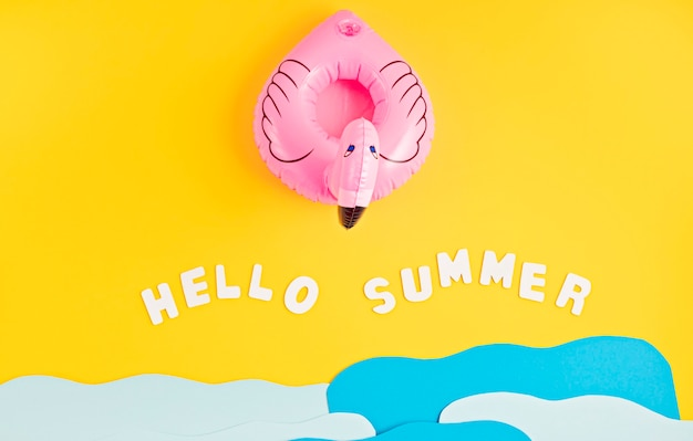 Inflatable pink flamingo, paper sea waves and text hello summer. summer vacations and beach, seaside holidays, parties concept