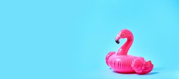 Надувная розовая игрушка для бассейна с фламинго на синем фоне. креативная минимальная концепция. баннер.