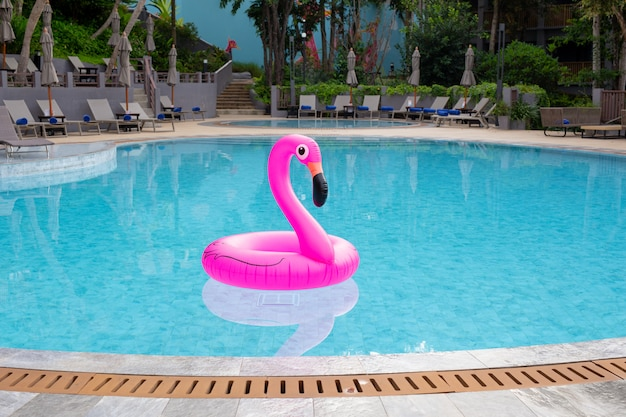 Inflatable pink flamingo in swimming pool. summer vacation.