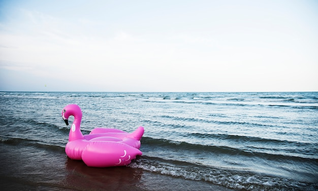 Inflatable pink flamingo tube on the beach