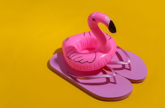 Inflatable pink flamingo with flip flops on yellow sunny background. summer, beach vacation concept. minimalism.