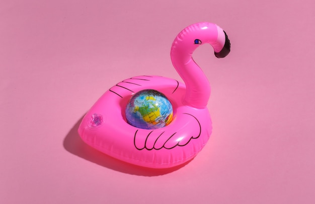 Inflatable pink flamingo with globe on pink sunny background. summer vacation concept.