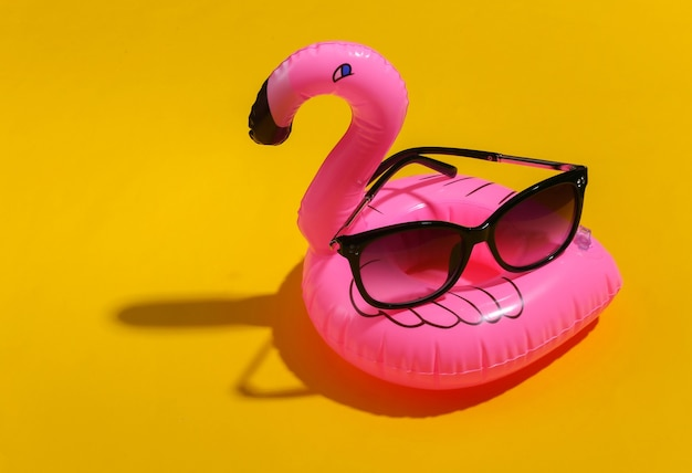 Inflatable pink flamingo with sunglasses on purple sunny background. summer vacation concept. minimalism