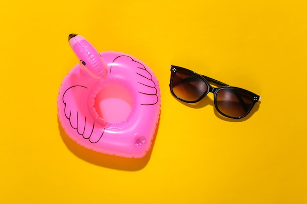 Inflatable pink flamingo with sunglasses on yellow sunny background. summer vacation concept. minimalism. top view.