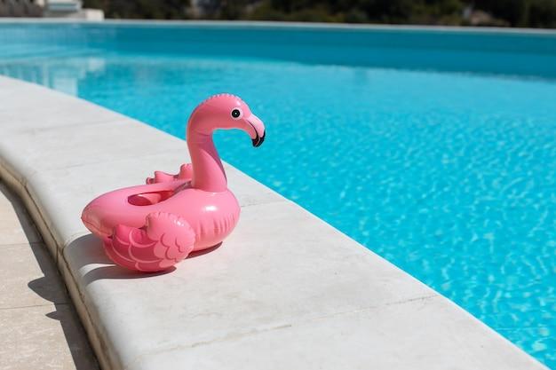 Надувной розовый мини-фламинго, коктейльная стойка возле бассейна в яркий солнечный день, копия пространства. концепция летних каникул, развлечений, воды, воздуха, принятия солнечных ванн, здоровья. вид сбоку. по горизонтали.