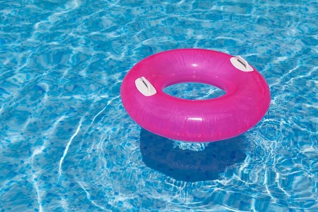 Надувное кольцо в бассейне сквозь воду отбрасывает тень на синюю мозаичную плитку искажение преломление