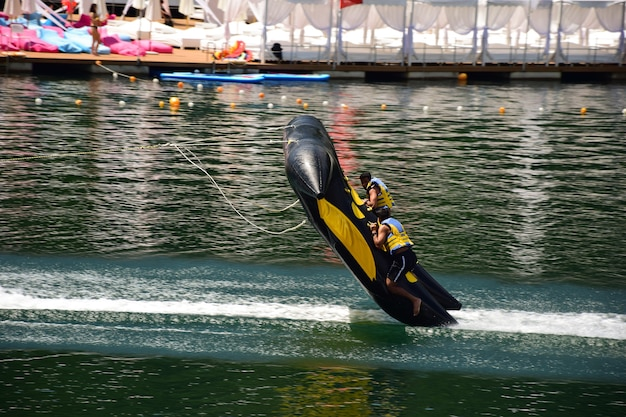 An inflatable sports raft with two men quickly floats through the water almost breaking away from
