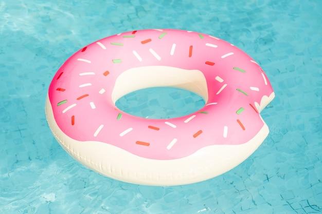 プールに浮かぶドーナツの形の膨脹可能な水泳リング