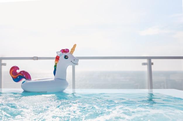 海の背景にあるプールの膨脹可能なユニコーンサークル。夏の背景。