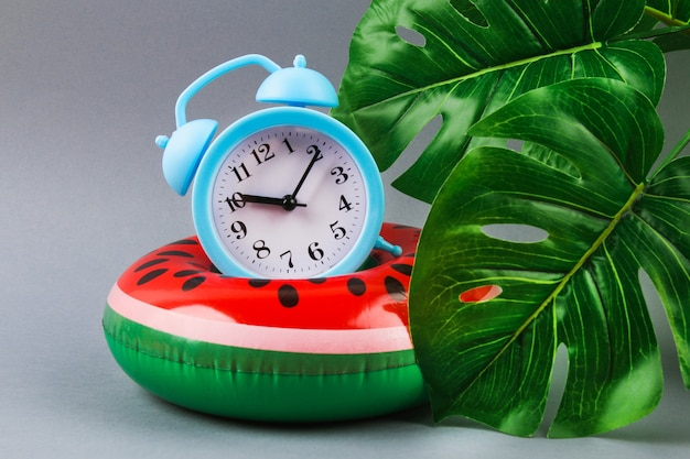 Inflatable watermelon on a grey background with monstera leaves and clock. summer concept of vacation.