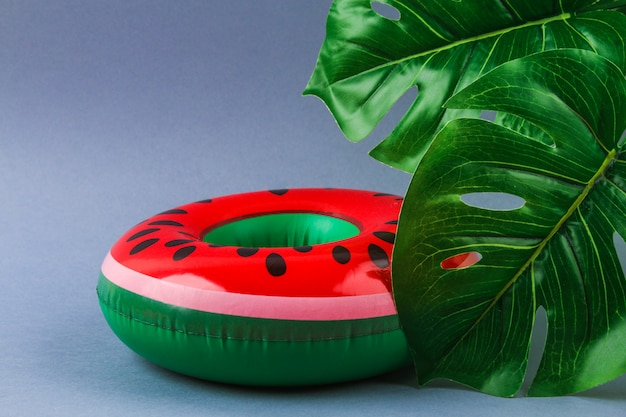 Inflatable watermelon on grey background with monstera leaves.